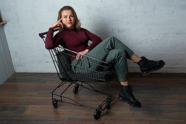 Eine frau in einem roten rollkragenpullover sitzt in einem einkaufskorb.