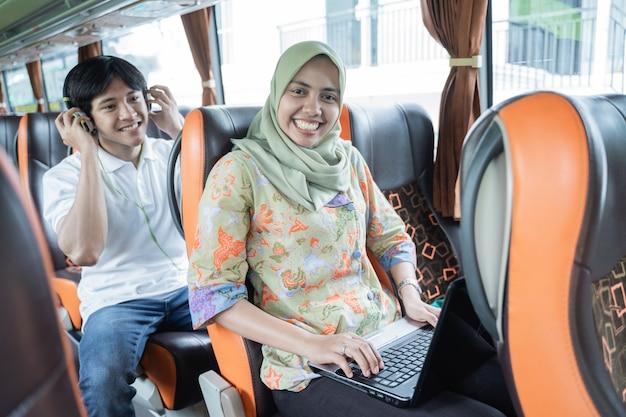 Eine frau in einem schleier lächelt, während sie einen laptop benutzt, und ein junger mann sitzt hinter ihr, während er im bus kopfhörer trägt