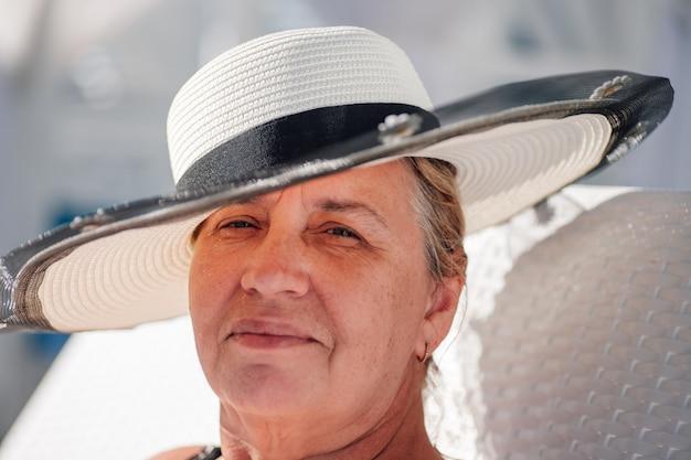 Eine frau in einem strohhut closeup portrait einer erwachsenen lächelnden frau in einem weißen strohhut auf einem hellen ...