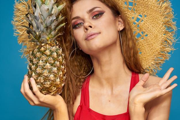 Eine frau in einem strohhut mit einer ananas in den händen oder ist es eine lustige blaue exotische frucht.