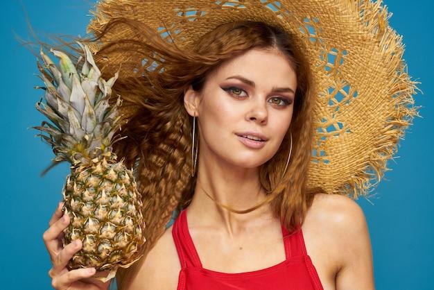 Eine frau in einem strohhut mit einer ananas in den händen oder ist es eine lustige blaue wand mit exotischen früchten.