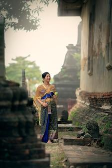 Eine frau in einem thailändischen kleid hält eine lotusblume in der hand, um die mönche im tempel vorzustellen.