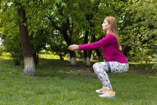 Eine frau in einem trainingsanzug macht ein sporttraining für den rücken mit fitness-gummibändern