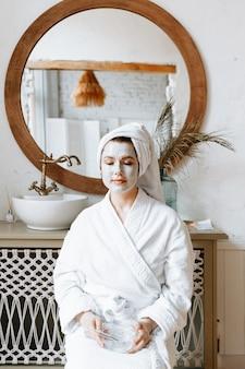 Eine frau in einem weißen bademantel und einem handtuch auf dem kopf posiert im badezimmer mit einer maske aus organischem ton im gesicht.