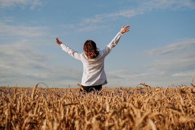Eine frau in einem weißen hemd auf einem roggenfeld. ansicht von hinten. das konzept von befriedung, meditation, glück, harmonie