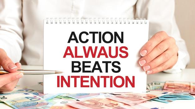 Eine frau in einem weißen hemd hält ein stück papier mit dem text: aktion immer beats absicht