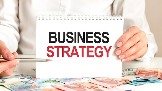 Eine frau in einem weißen hemd hält ein stück papier mit dem text: business strategy. mehrfarbige marker und tablette auf einem tisch. geschäftskonzept für unternehmen und bildungseinrichtungen.