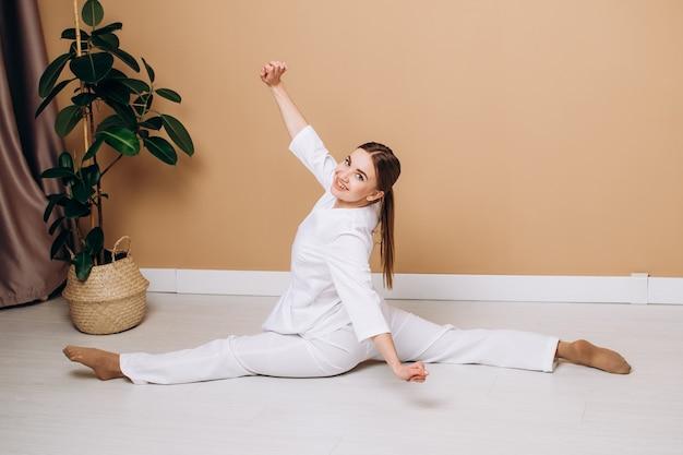 Eine frau in einem weißen kimono sitzt zu hause oder im fitnessstudio auf der schnur. üben sie einen gesunden lebensstil aus