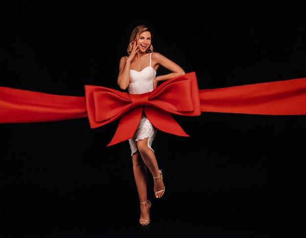 Eine frau in einem weißen kleid in form eines geschenks auf einem schwarzen ist in ein festliches band gewickelt.