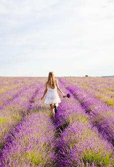 Eine frau in einem weißen kleid mit einem blumenstrauß ist ein blühendes lavendelfeld