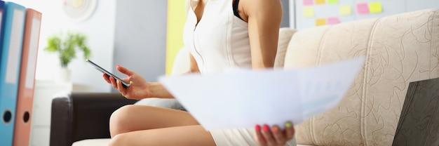 Eine frau in einem weißen kleid sitzt auf dem sofa im büro und schaut sich lächelnd ein dokument an