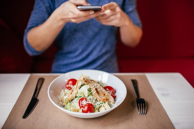 Eine frau in einer blauen bluse, die auf dem tisch foto des frischen salats caesar mit ihrem smartphone macht