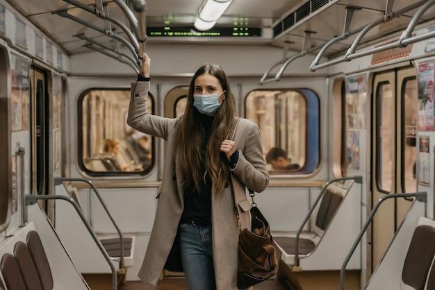Eine frau in einer gesichtsmaske, um die ausbreitung des coronavirus zu vermeiden, hält sich am handlauf fest und posiert in der mitte des u-bahnwagens. mädchen in einer chirurgischen maske gegen covid-19 steht in einem u-bahnzug