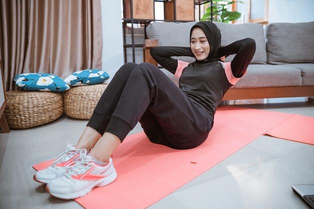 Eine frau in einer hijab-sportkleidung macht sit-ups, um ihre bauchmuskeln zu trainieren, während sie zu hause unterwegs ist