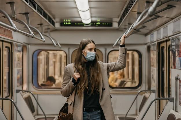 Eine frau in einer medizinischen gesichtsmaske an der u-bahnstation