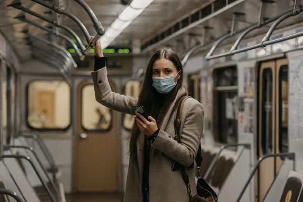 Eine frau in einer medizinischen gesichtsmaske posiert in einem u-bahn-wagen, um die ausbreitung des coronavirus zu vermeiden. ein mädchen mit langen haaren in einer operationsmaske im gesicht gegen covid-19 hält ein handy in einem zug.