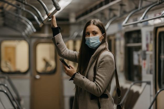 Eine frau in einer medizinischen gesichtsmaske, um die ausbreitung des coronavirus zu vermeiden, schaut sich in einem u-bahnwagen um. ein mädchen in einer operationsmaske im gesicht gegen covid-19 posiert mit einem handy in einem zug.