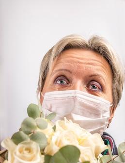 Eine frau in einer medizinischen maske mit einem blumenstrauß weint.
