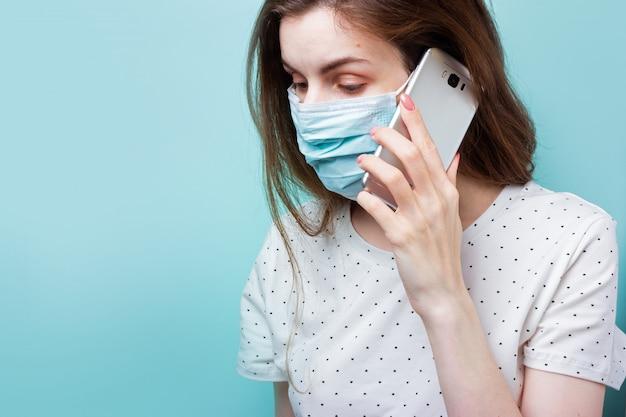 Eine frau in einer medizinischen schutzmaske telefoniert oder bestellt die lieferung von lebensmitteln.