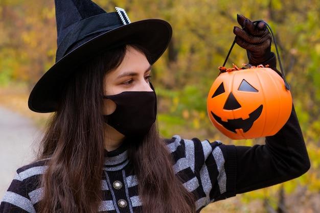 Eine frau in einer schutzmaske hält einen kürbis mit süßigkeiten.
