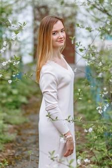 Eine frau in einer weißen bluse steht in einer kirschblüte