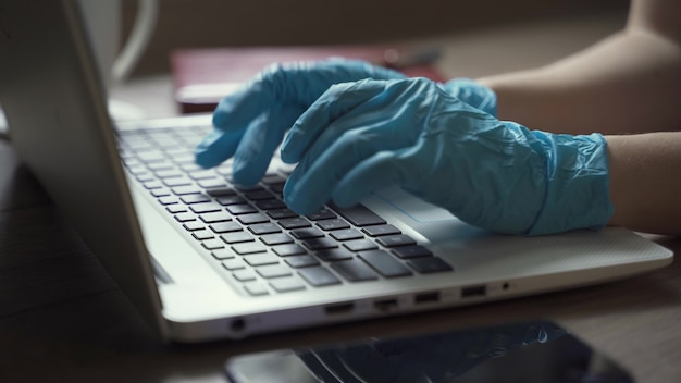Eine frau in einweghandschuhen mit einem laptop