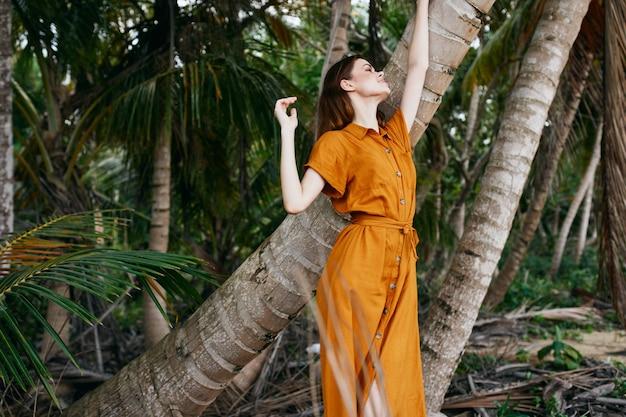 Eine frau in gelbem kleid und hut geht mit palmen am meer entlang am sand entlang