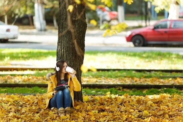 Eine frau in gelbem mantel und jeans sitzt mit einer tasse kaffee oder tee und hört musik unter einem baum mit einem tablet in den händen und kopfhörern im herbststadtpark an einem warmen tag. goldene herbstblätter.
