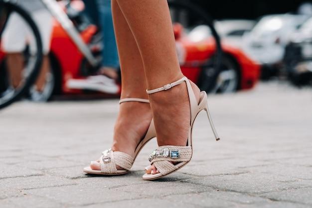 Eine frau in hochhackigen schuhen mit künstlichen diamanten in der stadt. schöne füße in schuhen nahaufnahme.