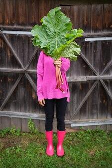 Eine frau in rosa stiefeln und einem rosa pullover hält einen strauß rhabarber in den händen.