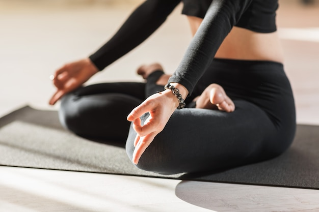 Eine frau in schwarzer sportbekleidung, die yoga praktiziert, meditiert im lotussitz und führt das kinn-mudra-symbol mit ihren händen aus