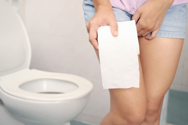 Eine frau in shorts und toilettenpapier geht ins badezimmer.