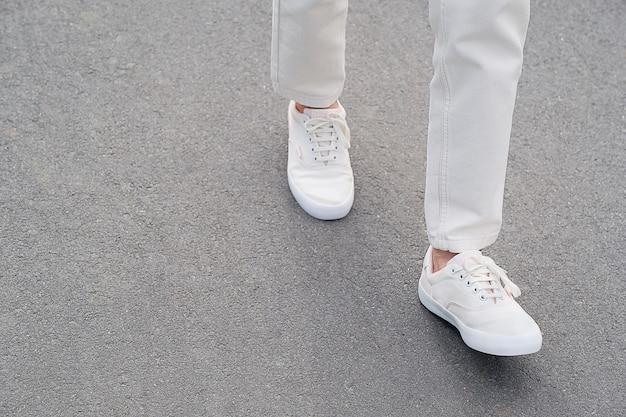 Eine frau in sportschuhen steht auf dem bürgersteig. beine eines mädchens in neuen weißen turnschuhen und jeans. modischer und stilvoller lebensstil.