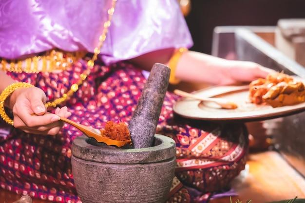 Eine frau in traditioneller thailändischer kleidung legt einen löffel in eine schüssel, um chilipaste aus einem mörser zu schöpfen.