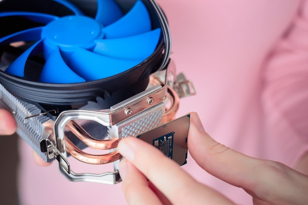 Eine frau installiert einen kühler mit aufgebrachter wärmeleitpaste an der cpu