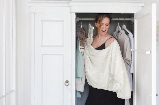 Eine frau ist in einem schrank mit unordentlichen kleidern überwältigt