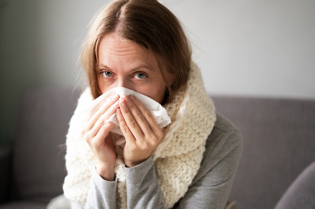 Eine frau ist zu hause krank, schnupfen und grippe