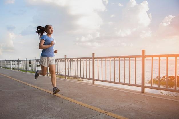 Eine frau joggt auf der brücke mit schönem sonnenlicht