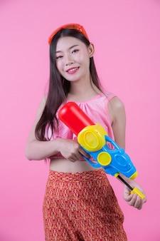 Eine frau kleidete in der traditionellen thailändischen volkskleidung an, die einen wasserwerfer auf einem rosa hintergrund hält.