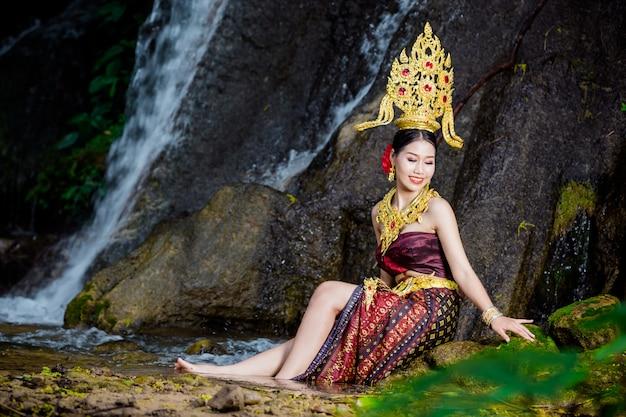 Eine frau kleidete sich mit einem alten thailändischen kleid am wasserfall an.
