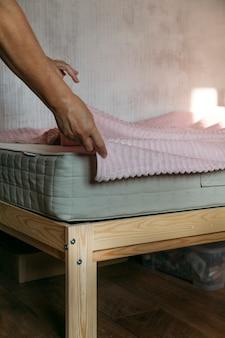 Eine frau legt eine matratze auf das bett oder verschiebt den reinigungsvorgang
