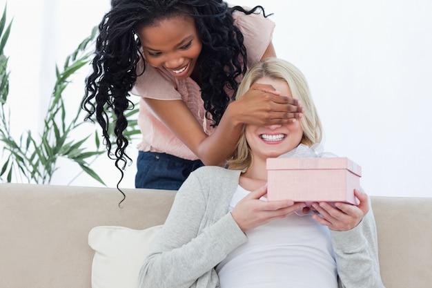 Eine frau legt ihre hand vor augen ihrer freunde, die ein geschenk halten