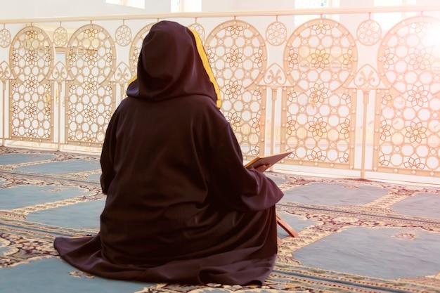 Eine frau liest den koran in der moschee, blick von hinten.