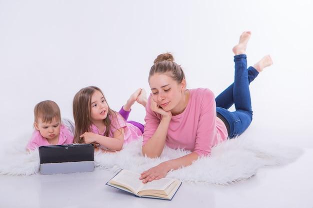 Eine frau liest ein buch, kinder schauen sich einen cartoon auf einem tablet an. hobbys und erholung mit gadgets. familienurlaub, zeit miteinander verbringen. heimunterricht
