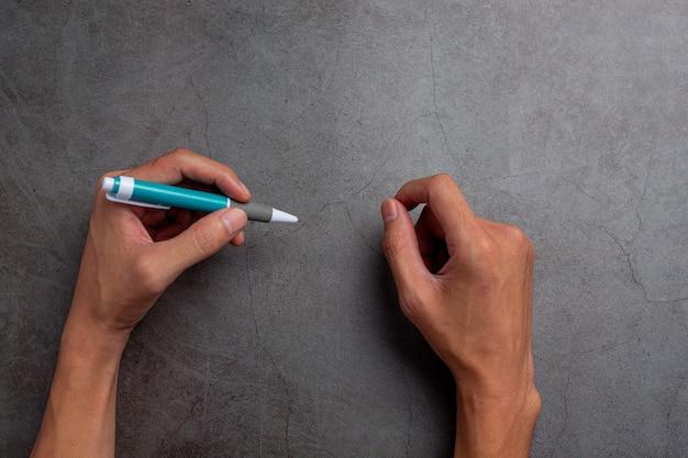 Eine frau linke hand mit einem stift. linkshänder tag konzept.