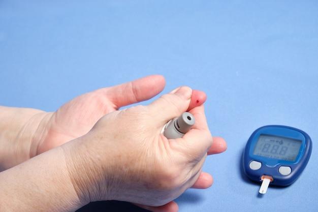 Eine frau macht eine blutuntersuchung auf zucker auf einem blauen feld. platz für text