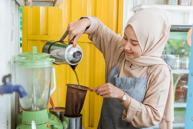 Eine frau macht getränk mit teesieb in ihrem kleinen straßenlebensmittelgeschäft