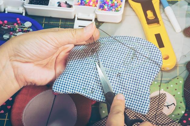 Eine frau macht handarbeit mit anderen stickereiausrüstungen auf einem tisch