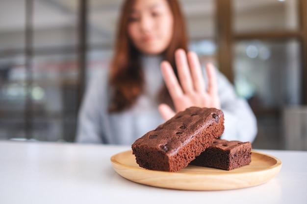 Eine frau macht handzeichen, um einen brownie-kuchen in holzplatte abzulehnen