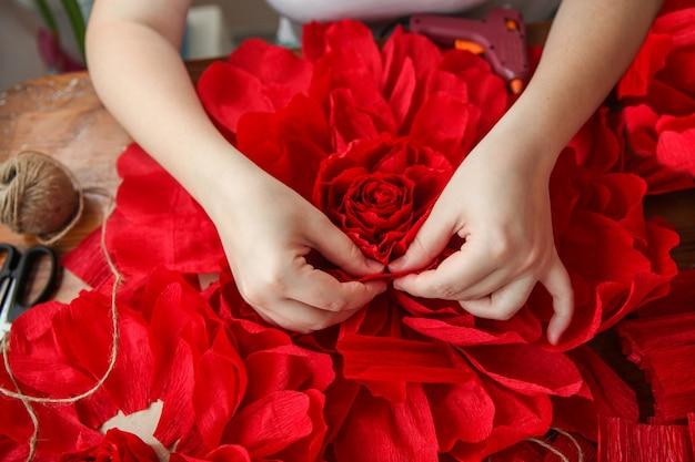 Eine frau macht rote papierblumen. nur die hände sind im rahmen. draufsicht. hochwertiges foto